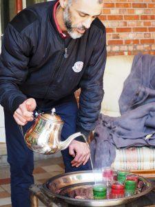 Said, één van de inwoners van de villa, trakteert bezoekers op verse muntthee